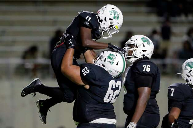 Spring wide receiver Travis Sims Jr. (11) is lifted by guard Kalvin Anaya (62) after Sims'  touchdown as Joziah Fogle (76) looks on during the first half of a high school football game Friday, Oct. 9, 2020 at Planet Ford Stadium in Spring, TX. Photo: Michael Wyke, Contributor / © 2020 Houston Chronicle