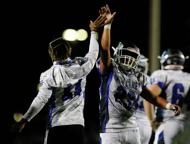gets a high-five from defensive back Cale Sanders, Jr. (11) after the team's 21-19 win over rival Porter during a District 8-5A high school football game at Randall Reed Stadium, Friday, Oct. 9, 2020, in Porter. Photo: Jason Fochtman, Staff Photographer / 2020 © Houston Chronicle