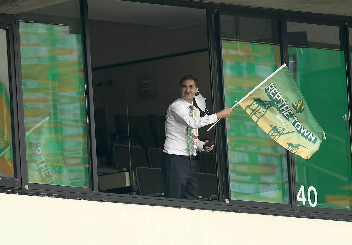A's team President Dave Kaval waves a flag repping Oakland after tying the game against the Chicago White Sox in the fourth inning of Game 3 of their AL wild card series at the Coliseum.