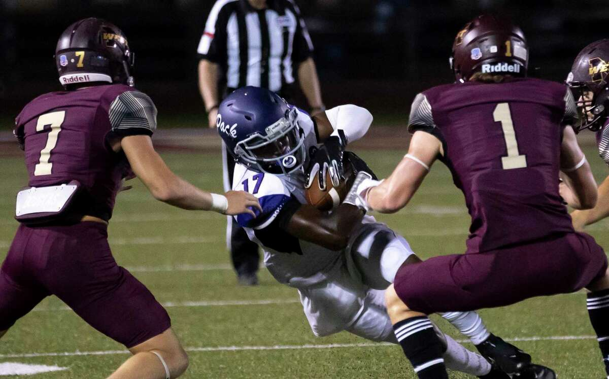Lufkin wide receiver Journie Thomas (17) protects the ball as he blocked by Magnolia West defensive back Tye Copeland (1) and defensive back Cody Costello (7) during the third quarter of a District 8-5A (Div. I) play at Mustang Stadium in Magnolia, Friday, Oct. 9, 2020.
