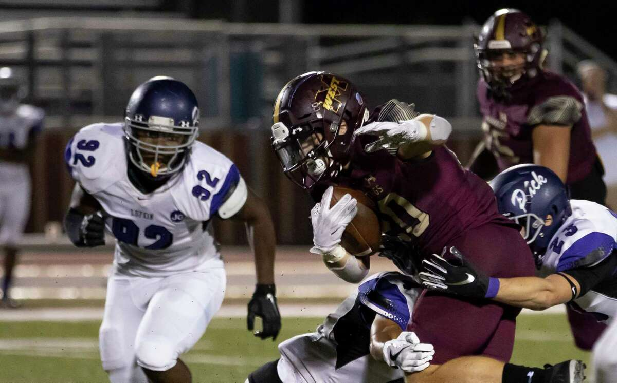 Magnolia West running back Hunter Bilbo (20) gets tackled by Lufkin safety Charlie Arnold (23), wide receiver Cristian Diaz (4) and linebacker Keelan Taylor (32) during the third quarter of a District 8-5A (Div. I) play at Mustang Stadium in Magnolia, Friday, Oct. 9, 2020.