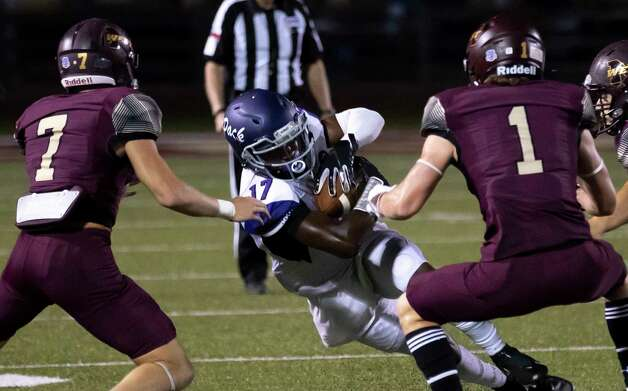 Lufkin wide receiver Journie Thomas (17) protects the ball as he blocked by Magnolia West defensive back Tye Copeland (1) and defensive back Cody Costello (7) during the third quarter of a District 8-5A (Div. I) play at Mustang Stadium in Magnolia, Friday, Oct. 9, 2020. Photo: Gustavo Huerta, Staff Photographer / 2020 © Houston Chronicle