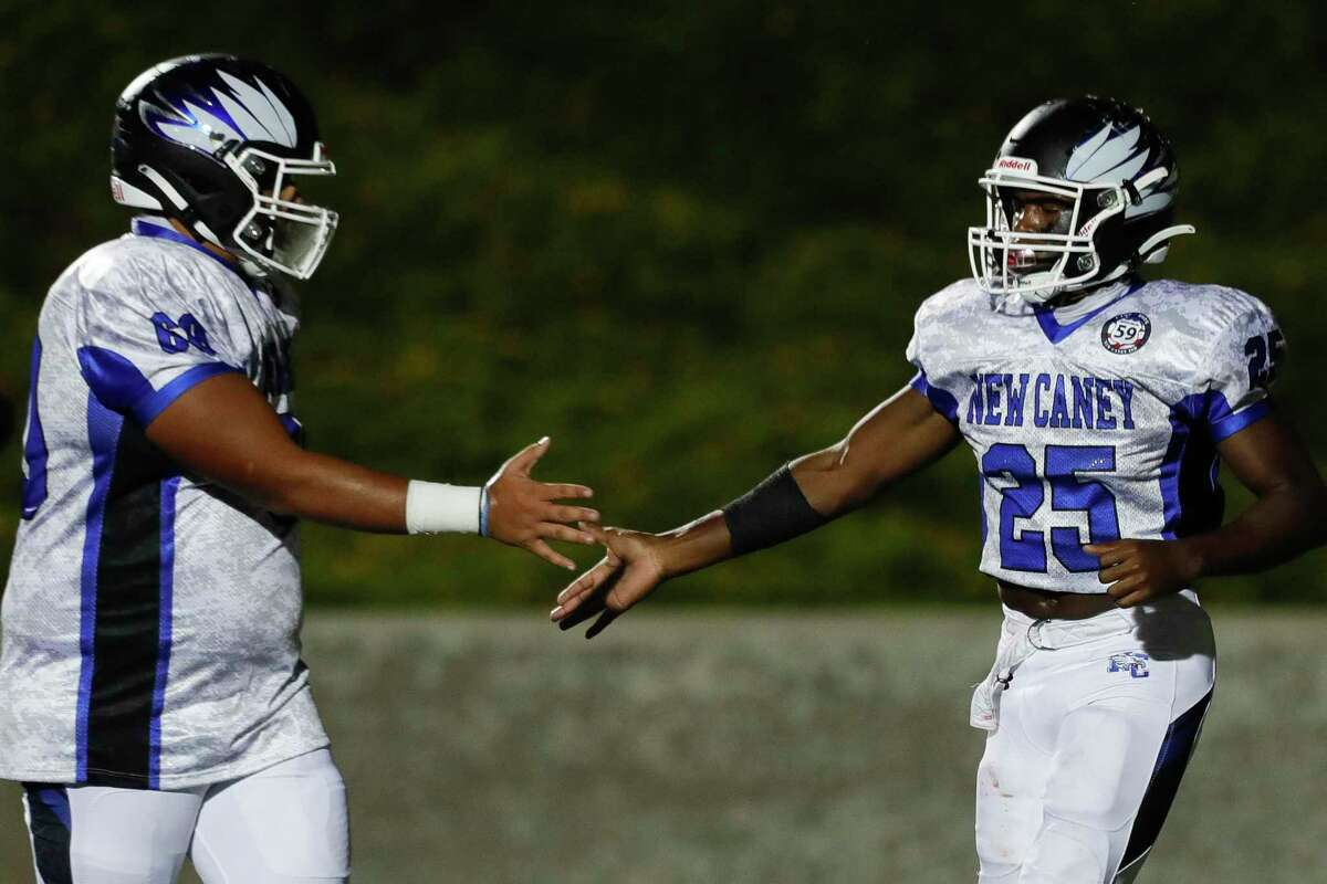 New Caney running back Kedrick Reescano (25) gets a high-five from offensive linemen Wyatt Hail (64) after scoring on a 2-yard run during the second quarter of a District 8-5A high school football game at Randall Reed Stadium, Friday, Oct. 9, 2020, in Porter.