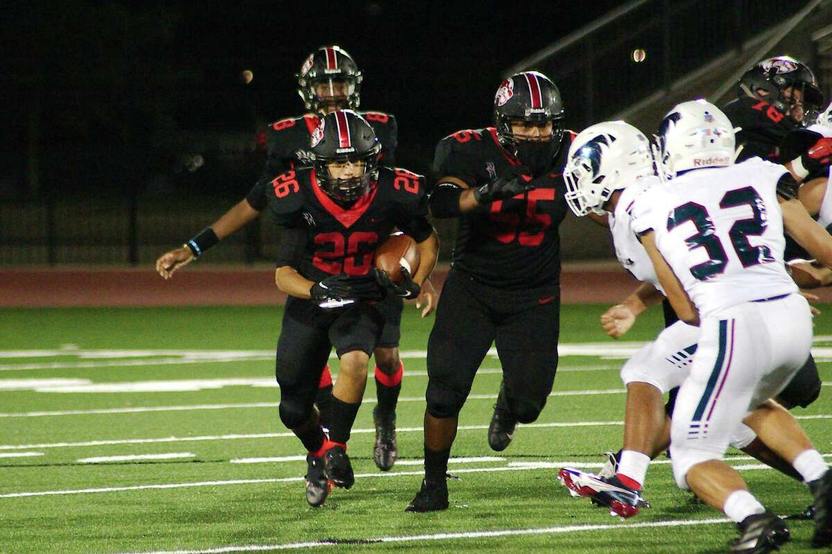 Clear Brook's Adrian Castillo (26) looks for running room behind the block of Clear Brook's Jim Rivera (55) against Clear Lake Friday, Oct. 9 at Challenger Columbia Stadium.
