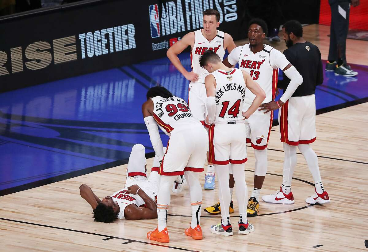 Miami's Jimmy Butler lays on the court after tipping in a basket despite a Dwight Howard flagrant foul in the third quarter.