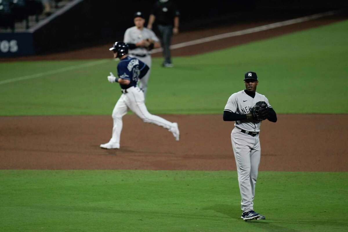 The New York Yankees' Aroldis Chapman waits for a new baseball as the Tampa Bay Rays' Michael Brosseau runs after hitting a solo home run during the eighth inning in Game 5 of the ALDS on Friday.