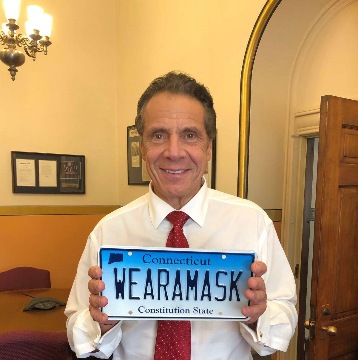 New York Gov. Andrew Cuomo displays a Connecticut license plate sent to him by Gov. Ned Lamont.