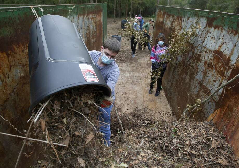 James Jacobs dumps a container of leaves and sticks into a dumpster as members of Boy Scout Troop 89 and other volunteers help clean debris from the Conroe Community Cemetery, Saturday, Oct. 10, 2020, in Conroe. The clean up day is part of the Conroe Community Cemetery Restoration ProjectÕs efforts to restore the site, which dates back to the 1890s and includes emancipated slaves, railroad workers, saw mill workers and the only confirmed Buffalo Solider buried in Montgomery County. Photo: Jason Fochtman/Staff Photographer / 2020 ? Houston Chronicle