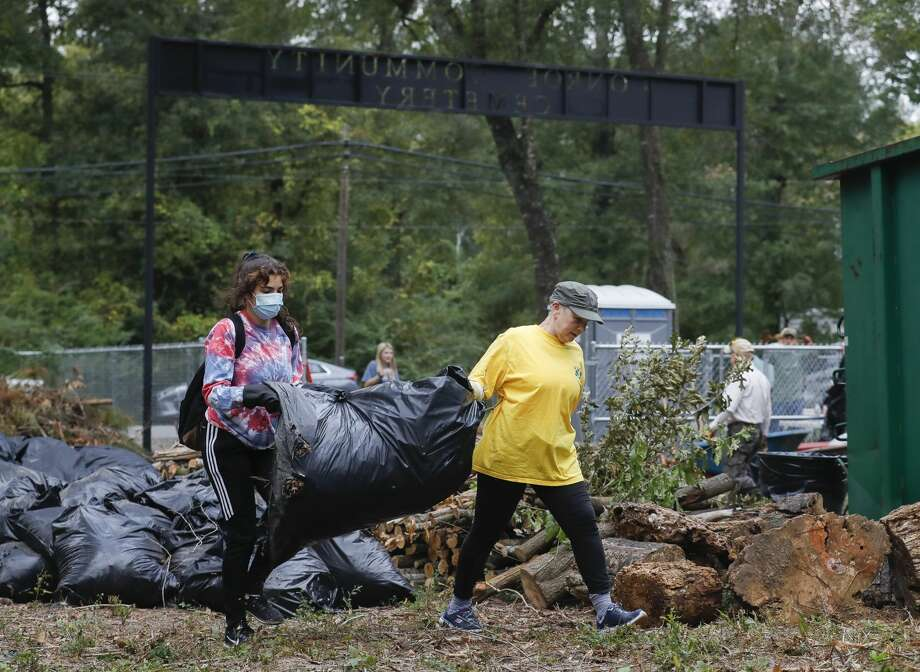 Joyce Pierce, right, and Natalie Branco carry a bag full of leaves and sticks as members of Boy Scout Troop 89 and other volunteers help clean debris from the Conroe Community Cemetery, Saturday, Oct. 10, 2020, in Conroe. The clean up day is part of the Conroe Community Cemetery Restoration ProjectÕs efforts to restore the site, which dates back to the 1890s and includes emancipated slaves, railroad workers, saw mill workers and the only confirmed Buffalo Solider buried in Montgomery County. Photo: Jason Fochtman/Staff Photographer / 2020 ? Houston Chronicle