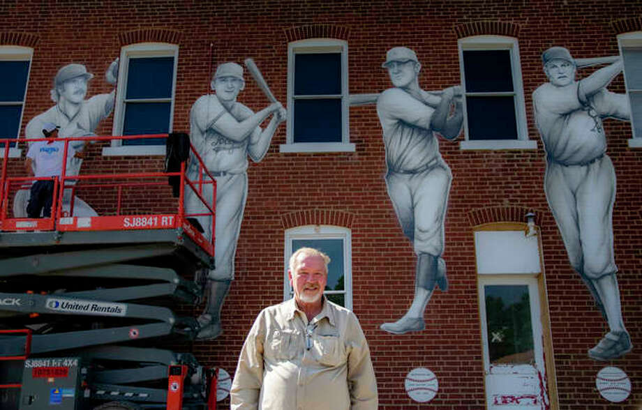 """Ken Oberkfell stands in front of a mural being painted on the east side of the Maryville Heritage Museum by Troy Freeman Wednesday. The mural includes images of Oberkfell, Dwain Sloat, John """"Buster"""" Lucas and Bob Boken. All were Major League Baseball players from Maryville. Photo: Tyler Pletsch 