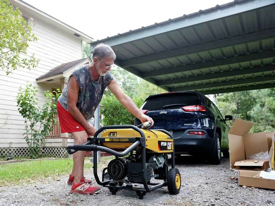 """Randy Philpott assembles a new generator as he prepares to ride out Hurricane Laura in his home in Bridge City on Wednesday, Aug. 26, 2020. Philpott is staying because his mom and aunt, who live close by, have decided not to leave. """"It's heck if you do, it's heck if you don't,"""" Photo: Elizabeth Conley, Houston Chronicle / Staff Photographer / © 2020 Houston Chronicle"""