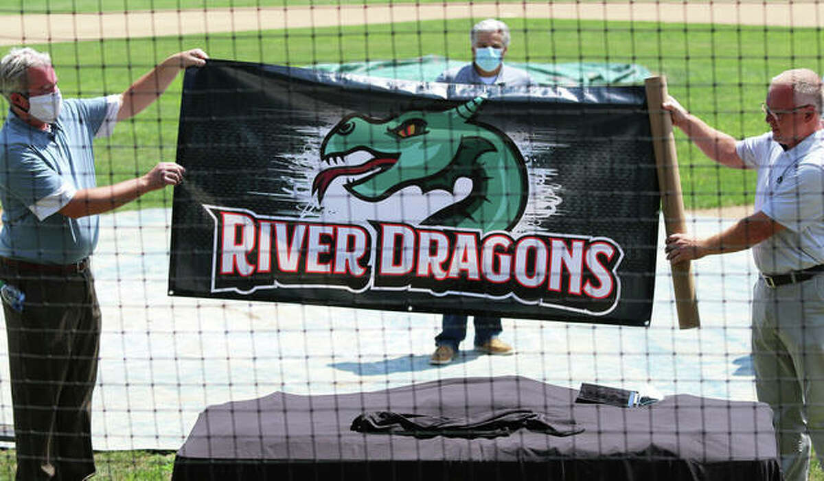 Alton River Dragons owner Steve Marso and team general manager Dallas Marso display the new banner touting the Alton River Dragons logo during a ceremony at Lloyd Hopkins Field in Gordon Moore Park.