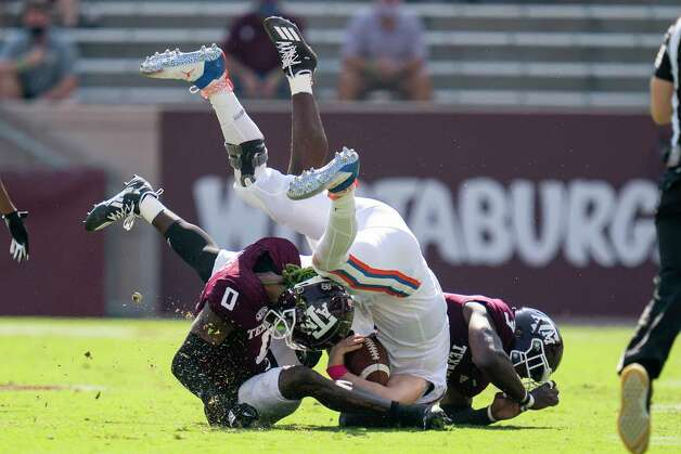 Florida quarterback Kyle Trask (11) is tackled after a short gain by Texas A&M defensive lineman Tyree Johnson (3) and defensive back Myles Jones (0) during the first quarter of an NCAA college football game, Saturday, Oct. 10, 2020. in College Station, Texas. (AP Photo/Sam Craft) Photo: Sam Craft, Associated Press / Copyright 2020 The Associated Press. All rights reserved.