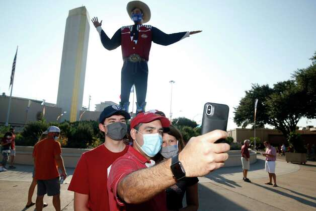 """Oklahoma fans Lucas Aleman, Josias Aleman and Annie Aleman, of Kansas City, take a selfie in front of """"Big Tex"""" prior to an NCAA college football game between University of Texas and Oklahoma. in Dallas,  Saturday, Oct. 10, 2020. (AP Photo/Michael Ainsworth) Photo: Michael Ainsworth, Associated Press / Copyright 2020 The Associated Press. All rights reserved."""