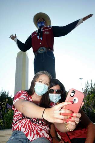 """Oklahoma fans Emily Boyers, of Fort Smith, Ark., and her mother Lisa Martin, of Muldrow, Okla., take a selfie in front of """"Big Tex"""" prior an NCAA college football game between the University of Texas and Oklahoma. in Dallas,  Saturday, Oct. 10, 2020. (AP Photo/Michael Ainsworth) Photo: Michael Ainsworth, Associated Press / Copyright 2020 The Associated Press. All rights reserved."""