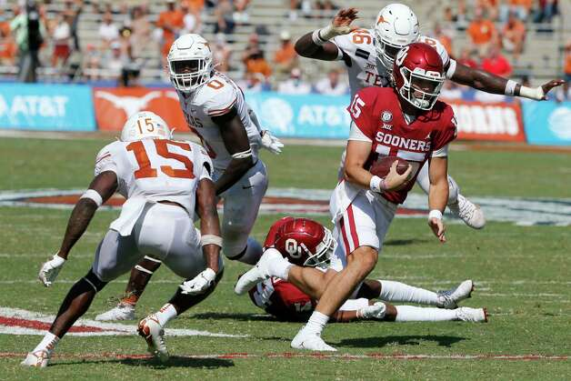 Oklahoma quarterback Tanner Mordecai (15) tries to get past Texas defensive back Chris Brown (15) during an NCAA college football game in Dallas, Saturday, Oct. 10, 2020. (AP Photo/Michael Ainsworth) Photo: Michael Ainsworth, Associated Press / Copyright 2020 The Associated Press. All rights reserved.