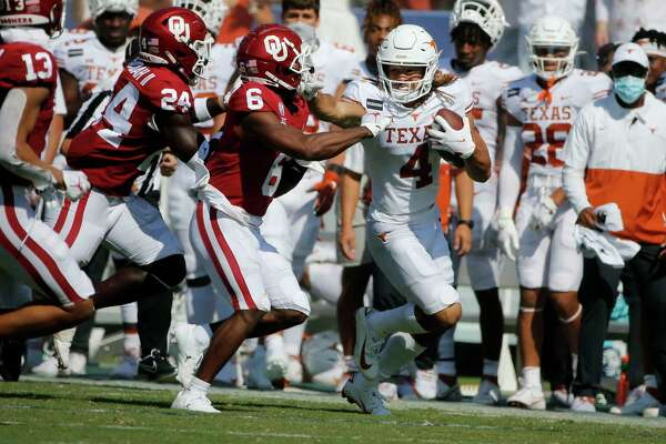 Texas wide receiver Jordan Whittington (4) tries to stiff-arm Oklahoma defensive back Tre Brown (6) after a reception during an NCAA college football game in Dallas, Saturday, Oct. 10, 2020. (AP Photo/Michael Ainsworth)
