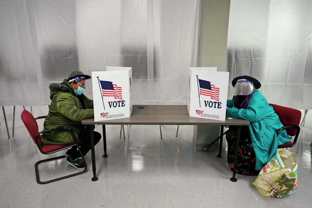 FILE - In this Oct. 6, 2020, file photo two voters fill out ballots during early voting at the Cuyahoga County Board of Elections in Cleveland.