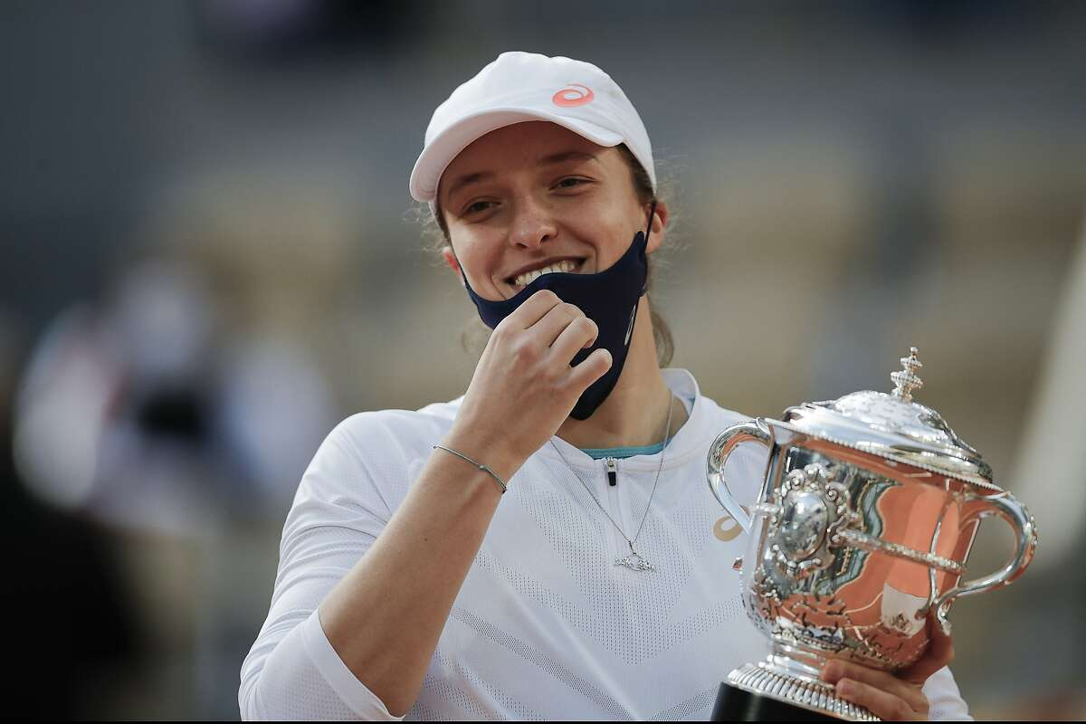 Poland's Iga Swiatek holds the trophy after winning the final match of the French Open tennis tournament against Sofia Kenin of the U.S. in two sets 6-4, 6-1, at the Roland Garros stadium in Paris, France, Saturday, Oct. 10, 2020. (AP Photo/Christophe Ena)
