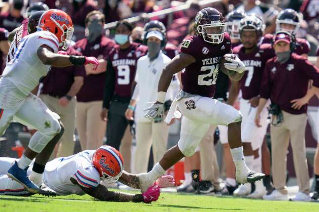 Texas A&M running back Isaiah Spiller (28) steps away from Florida linebacker Brenton Cox Jr. (1) during a run down the sideline during the second half of an NCAA college football game, Saturday, Oct. 10, 2020. in College Station, Texas. (AP Photo/Sam Craft) Photo: Sam Craft, Associated Press / Copyright 2020 The Associated Press. All rights reserved.