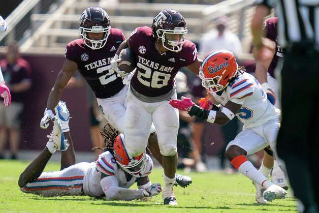 Texas A&M running back Isaiah Spiller (28) stiff arms Florida defensive back Chester Kimbrough (25) during a run during the second half of an NCAA college football game, Saturday, Oct. 10, 2020. in College Station, Texas. (AP Photo/Sam Craft) Photo: Sam Craft, Associated Press / Copyright 2020 The Associated Press. All rights reserved.
