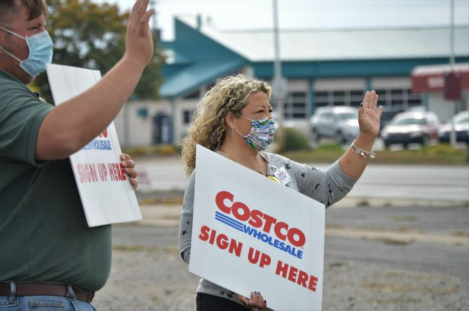 Midland resident and front-end assistance, Jordan Starks, and front-end assistant from Toledo, Katina Ortega, wave to passing drivers, encouraging them to stop and sign up for a Costco membership. (Ashley Schafer/ashley.schafer@hearstnp.com) Photo: Ashley Schafer