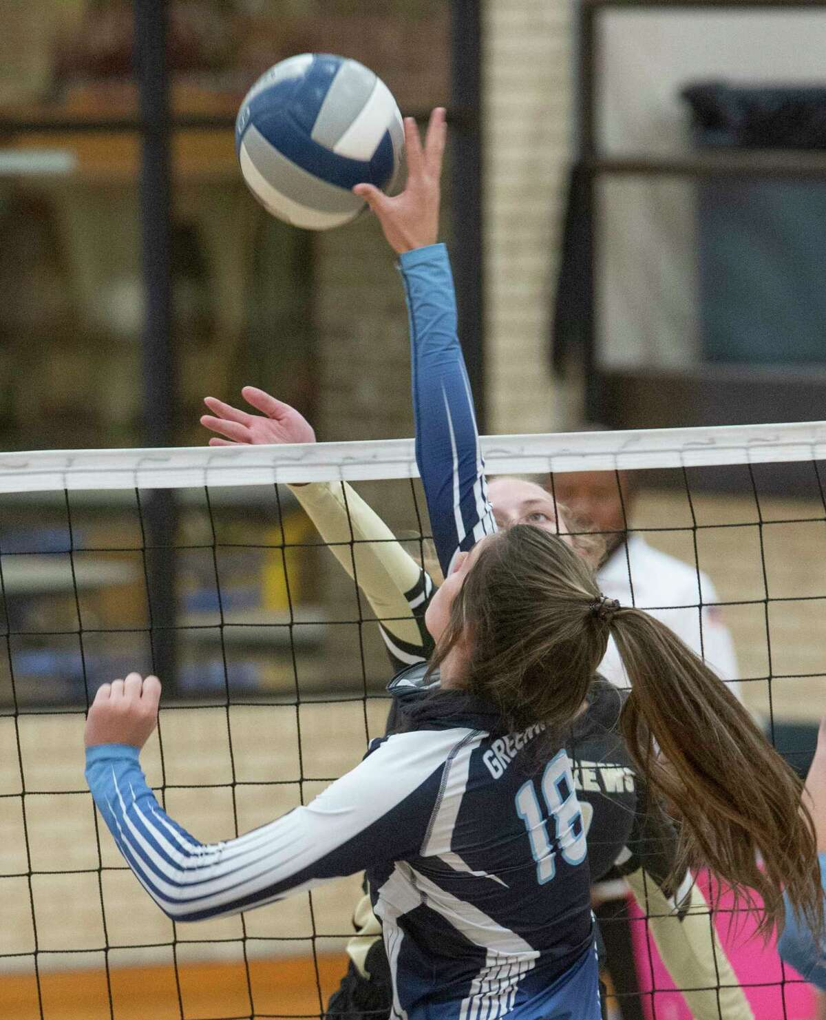 Greenwood's Mackenzie Brockman looks to tip the ball away from the reach of Andrews' Kassidy Epperson 10/10/2020 at Greenwood High gym. Tim Fischer/Reporter-Telegram