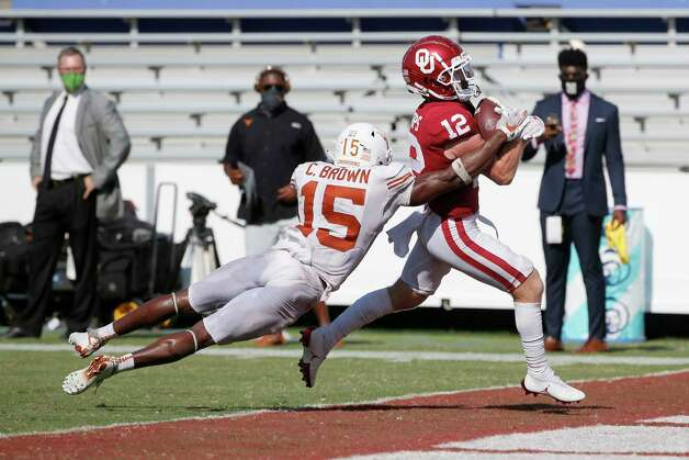 Oklahoma wide receiver Drake Stoops (12) scores the winning touchdown in overtime as Texas defensive back Chris Brown (15) tries to tackle him during an NCAA college football game in Dallas,Tx, Saturday, Oct. 10, 2020. Oklahoma defeated Texas 53-45 in four overtimes.(AP Photo/Michael Ainsworth) Photo: Michael Ainsworth, Associated Press / Copyright 2020 The Associated Press. All rights reserved.