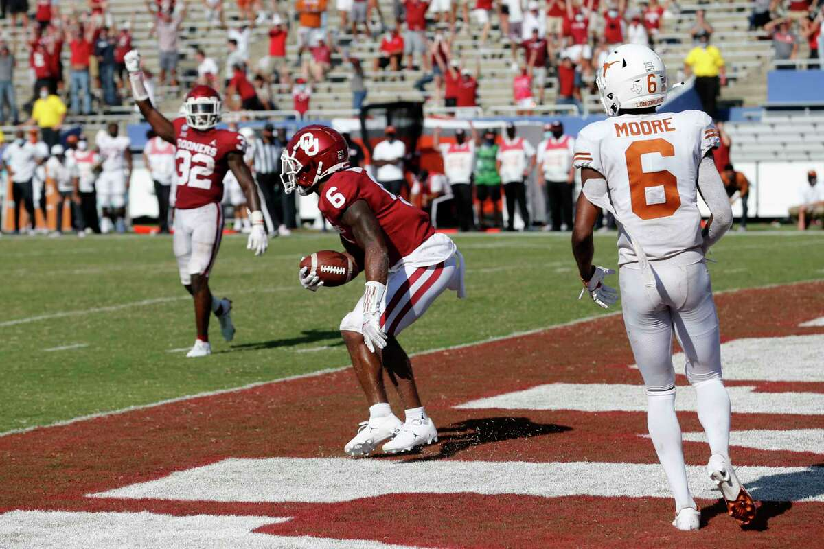 Oklahoma defensive back Delarrin Turner-Yell (32) celebrates as defensive back Tre Brown (6) makes the game-winning interception of a pass intended for Texas wide receiver Joshua Moore (6) during the fourth overtime period in an NCAA college football game in Dallas,Tx, Saturday, Oct. 10, 2020. Oklahoma defeated Texas 53-45 in overtime.(AP Photo/Michael Ainsworth)
