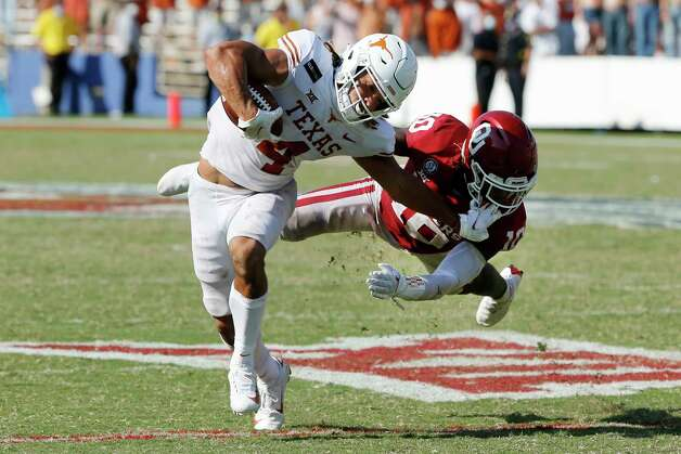 Texas wide receiver Jordan Whittington (4) tries to break a tackle from Oklahoma defensive back Pat Fields (10) during overtime of an NCAA college football game in Dallas, Saturday, Oct. 10, 2020. Oklahoma defeated Texas 53-45 in four overtimes.(AP Photo/Michael Ainsworth) Photo: Michael Ainsworth, Associated Press / Copyright 2020 The Associated Press. All rights reserved.