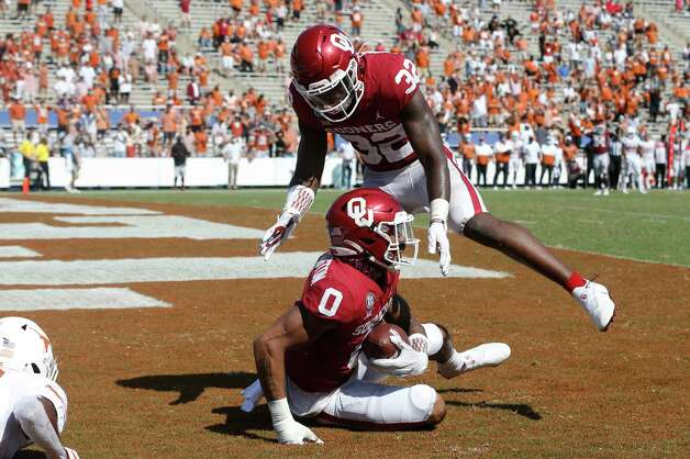 Oklahoma defensive back Delarrin Turner-Yell (32) celebrates after defensive back Woodi Washington (0) made an interception against Texas during the second half of an NCAA college football game in Dallas, Saturday, Oct. 10, 2020. Oklahoma defeated Texas 53-45 in four overtimes. (AP Photo/Michael Ainsworth) Photo: Michael Ainsworth, Associated Press / Copyright 2020 The Associated Press. All rights reserved.