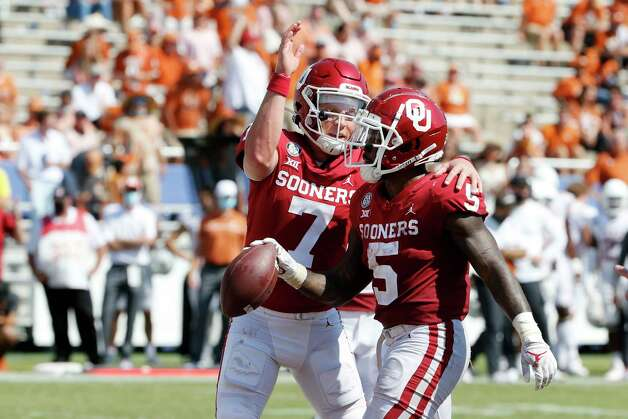 Oklahoma quarterback Spencer Rattler (7) congratulates running back T.J. Pledger (5) after Pledger scored against Texas during the second half of an NCAA college football game in Dallas, Saturday, Oct. 10, 2020. Oklahoma defeated Texas 53-45 in four overtimes. (AP Photo/Michael Ainsworth) Photo: Michael Ainsworth, Associated Press / Copyright 2020 The Associated Press. All rights reserved.