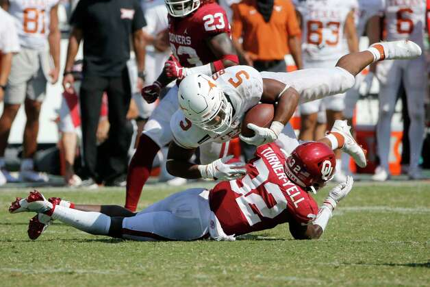Oklahoma defensive back Delarrin Turner-Yell (32) upends Texas running back Bijan Robinson (5) during the second half of an NCAA college football game in Dallas, Saturday, Oct. 10, 2020. Oklahoma defeated Texas 53-45 in four overtimes.(AP Photo/Michael Ainsworth) Photo: Michael Ainsworth, Associated Press / Copyright 2020 The Associated Press. All rights reserved.
