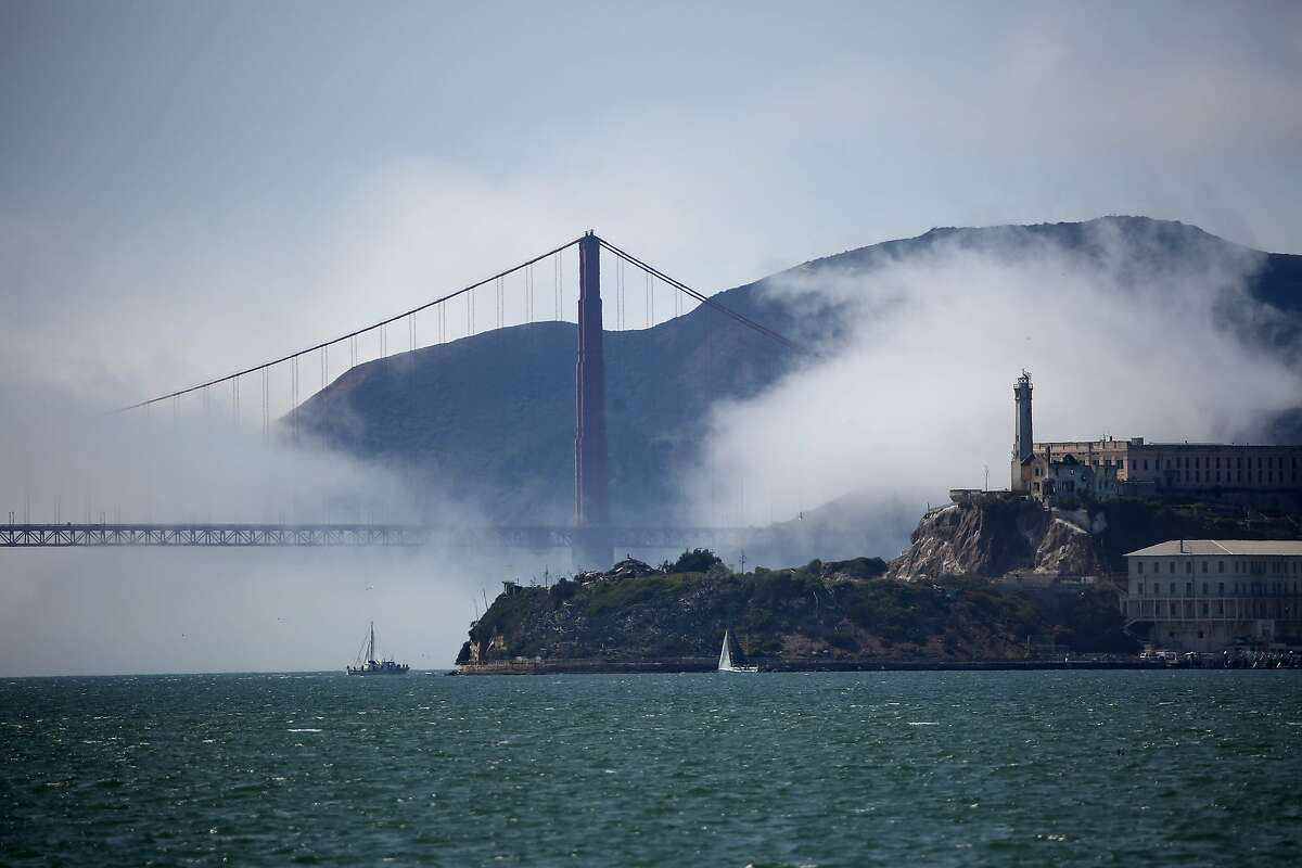 Low fog swirls around Alcatraz and the Golden Gate Bridge under clear skies as boats sail on the San Francisco Bay. A group of Bay Area lawmakers want more federal dollars invested into the bay's restoration.