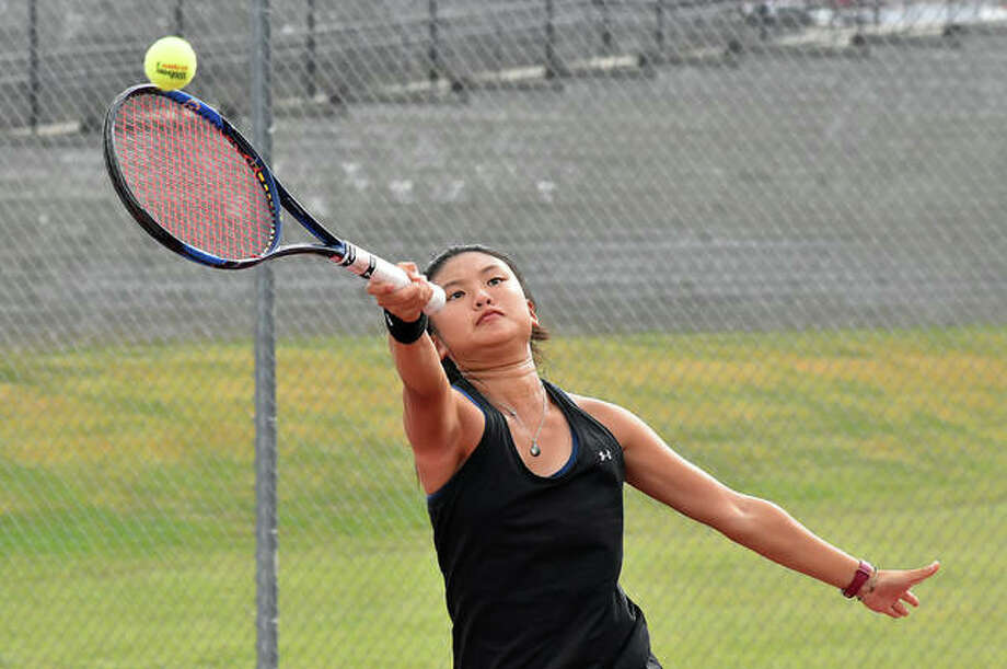 Edwardsville's Chloe Koons reaches high for a shot during her semifinal match in the No. 1 singles flight of the Southwestern Conference Tournament on Saturday at Alton High School. Photo: Matt Kamp|The Intelligencer
