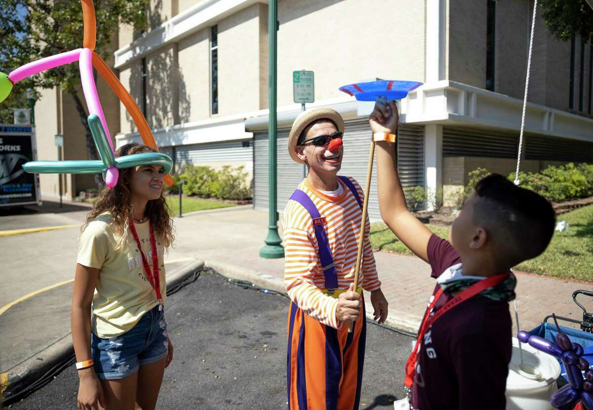 Aaliyah Willis, left watches her brother Gavin play with Roly the clown during the Conroe Cajun Catfish Festival, Saturday, Oct. 10, 2020 in downtown Conroe. Attendance is expected to be greater than previous years according to the Friends of Conroe.