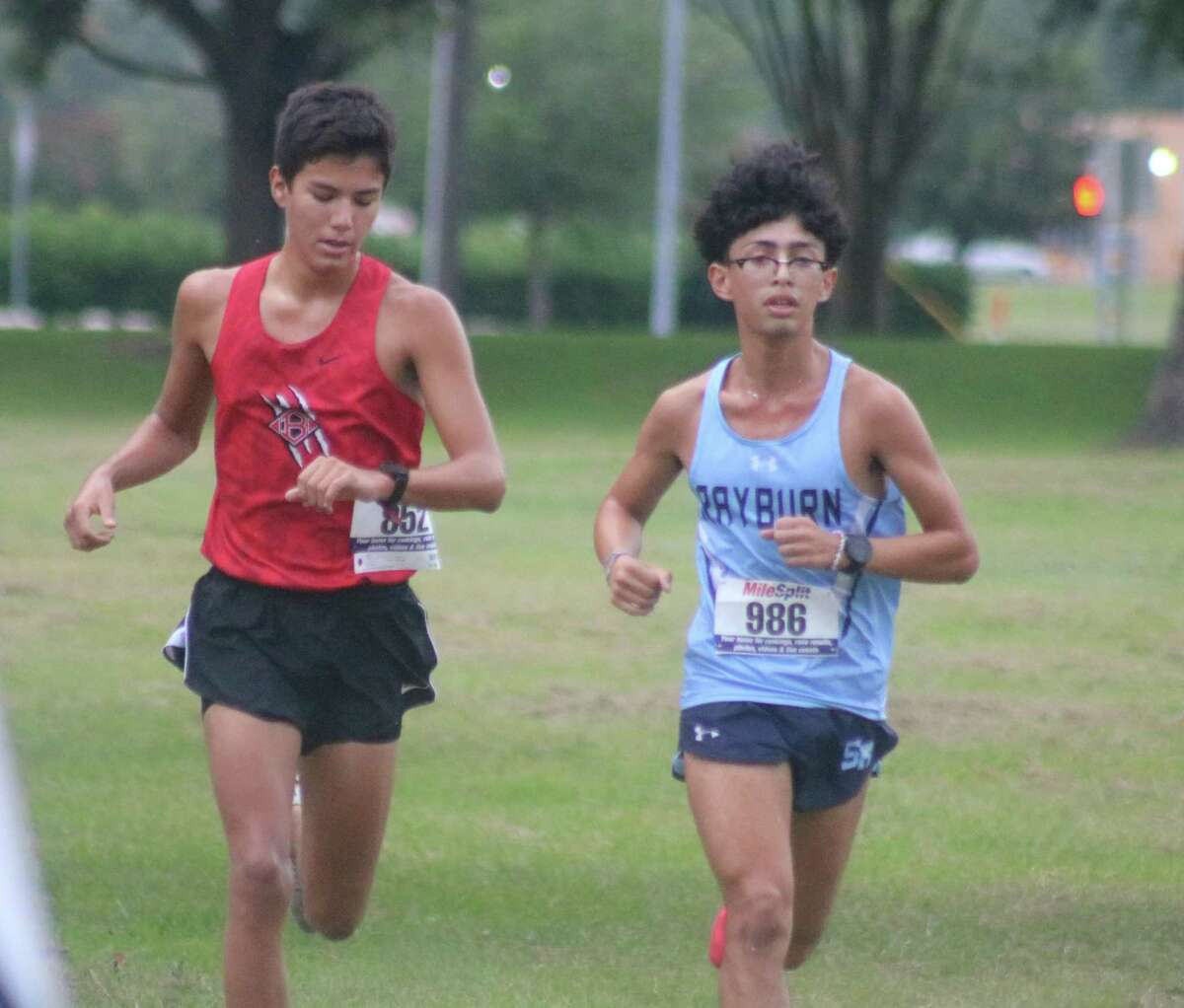 Clear Brook's Matthew Trevino (left) and Sam Rayburn's Jonathan Rivera are shoulder-to-shoulder in contesting first place during the Red Division 5K race at Crenshaw Park last Thursday morning.