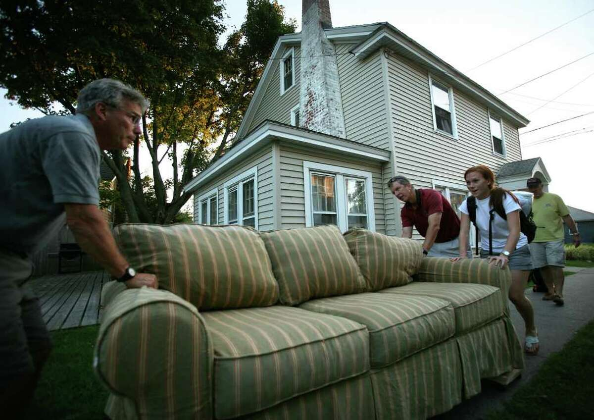 Jim Romanelli, left of Branford, helps his daughter Hollis, 21, a senior at Fairfield University, move a couch to her beachfront rental in Fairfield. Her roomate's father, Jim Gover of Bridgewater, NJ, also helps with move.