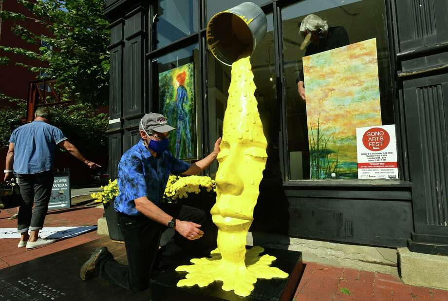 Sculptor Michael Alfano adjusts his sculpture outside a vacant storefront as the SoNo Arts Festival introduces their first-ever Gallery Walk along Washington Street Historic District Saturday, October 10, 2020, in South Norwalk. The event took place in available retail properties along Washington Street, part of AGW SoNo Partners' newly acquired portfolio. Over 50 juried artists will house, display, and sell their works inside these unique retail and restaurant spaces through Sunday. Photo: Erik Trautmann / Hearst Connecticut Media / Norwalk Hour