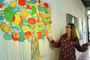 Aritist Katy Sullivan hangs her work in a vacant retail space the SoNo Arts Festival introduces their first-ever Gallery Walk along Washington Street Historic District Saturday, October 10, 2020, in South Norwalk. The event was so popular, it was extended to a third weekend starting Oct. 22, 2020.