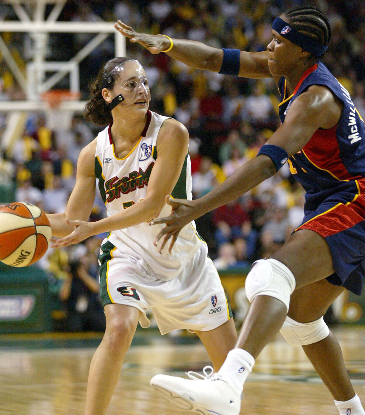 Seattle Storm guard Sue Bird, left, passes around Connecticut Sun center Taj McWilliams-Franklin in the 1st half Tuesday, Oct. 12, 2004 in Game 3 of the WNBA Finals at Key Arena in Seattle.