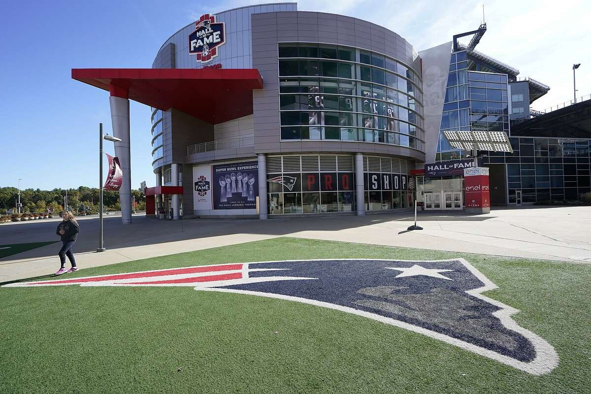 A passer-by walks past a New England Patriots football team logo near the Patriots ProShop at Gillette Stadium on Sunday in Foxborough, Mass. The NFL has postponed the Denver Broncos-New England Patriots game due to another positive coronavirus test with the Patriots.