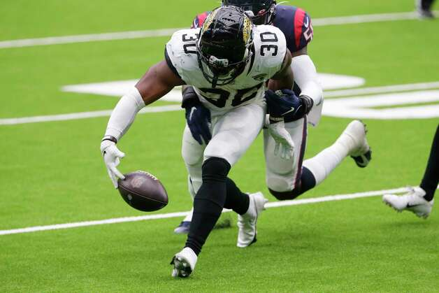 Jacksonville Jaguars running back James Robinson (30) fumbles as he is hit by Houston Texans linebacker Tyrell Adams (50) during the second half of an NFL football game Sunday, Oct. 11, 2020, in Houston. (AP Photo/Michael Wyke) Photo: Michael Wyke, Associated Press / Copyright 2019 The Associated Press. All rights reserved.