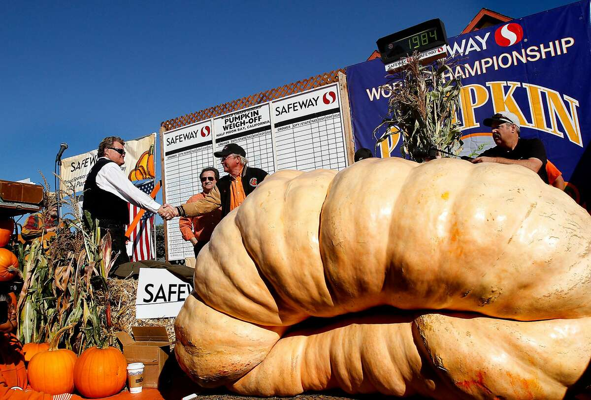 Gary Miller (center) is congratulated for his winning 1,985-pound pumpkin at the 40th annual Half Moon Bay pumpkin contest in 2013. Miller's pumpkin was not large enough to break the world record, but it was big enough to win the contest that October day.
