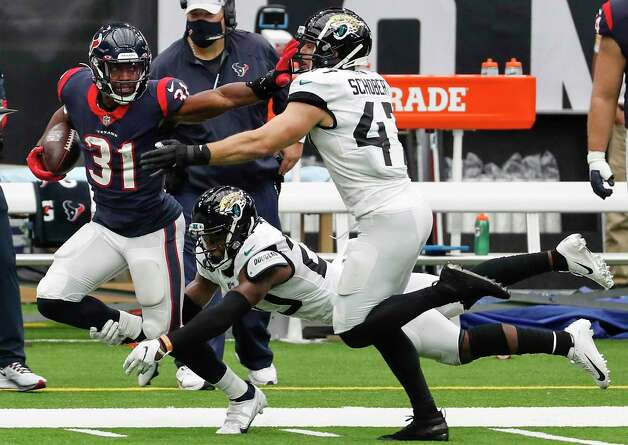 Houston Texans running back David Johnson (31) puts out an arm to fend of the defenders as he runs for a first down past Jacksonville Jaguars middle linebacker Joe Schobert (47) and safety Daniel Thomas (20) during the fourth quarter of an NFL football game at NRG Stadium on Sunday, Oct. 11, 2020, in Houston. Photo: Brett Coomer, Staff Photographer / © 2020 Houston Chronicle