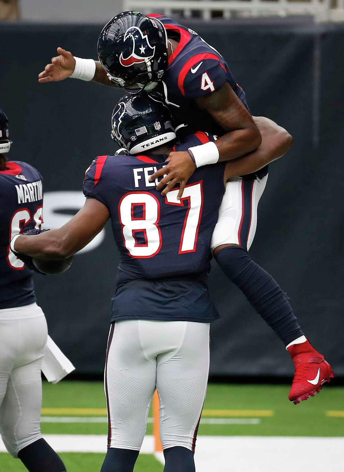 Houston Texans quarterback Deshaun Watson (4) leaps into the arms of tight end Darren Fells (87) as they celebrate Fells' 44--yard touchdown reception against the Jacksonville Jaguars during the first half of an NFL football game at NRG Stadium on Sunday, Oct. 11, 2020, in Houston.