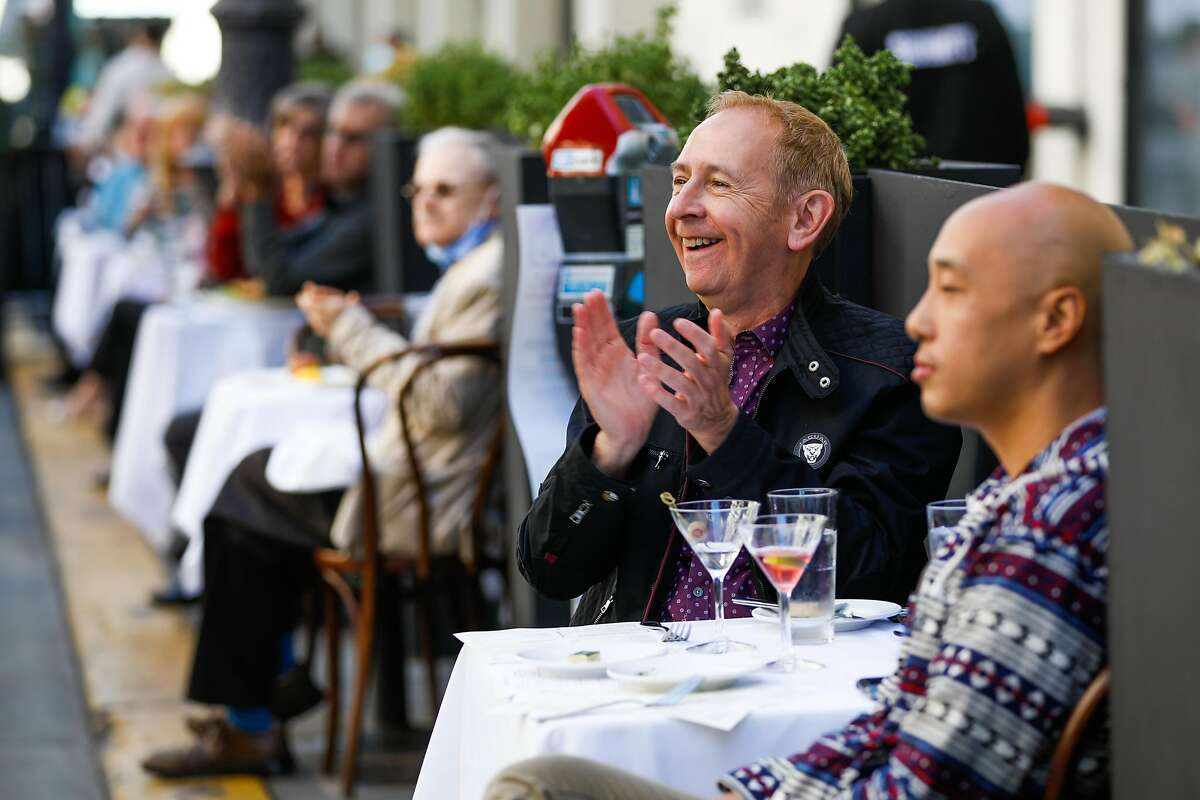 Dan Craft (center) applauds as Smuin Contemporary Ballet dancers perform for diners at John's Grill Oasis on Ellis Street on Sunday in San Francisco.