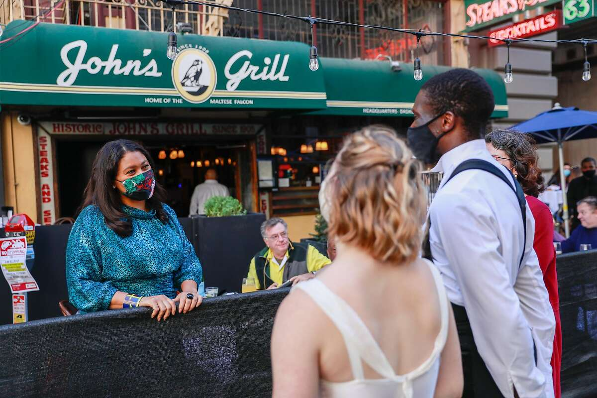 San Francisco Mayor London Breed (left) visits with Smuin Contemporary Ballet dancers Cassidy Isaacson and Brandon Alexander outside John's Grill.