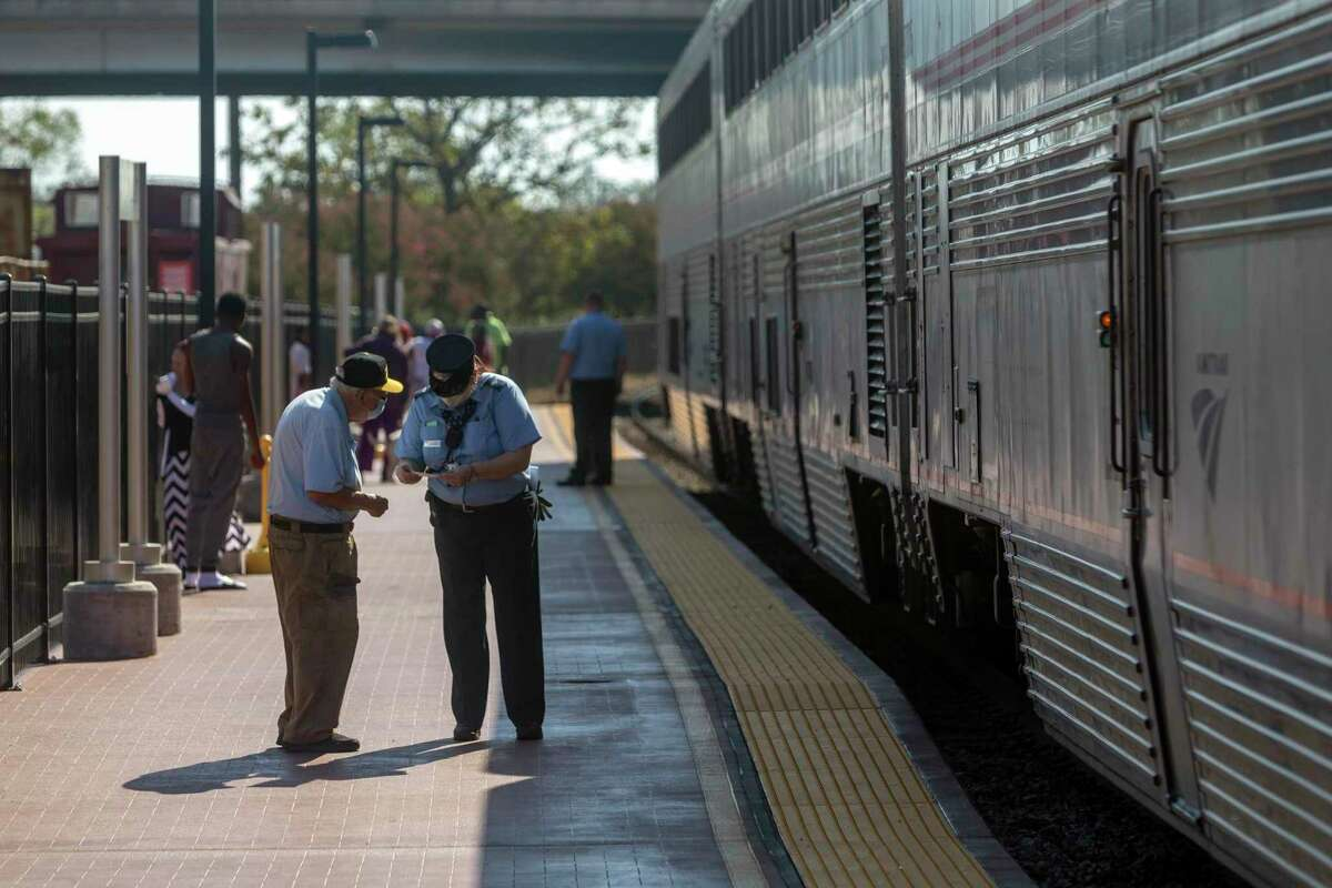 Assistant conductor Beronique Galvan, right, helps a person Sunday, Oct. 11, 2020 on the platform at the Temple Amtrak station. Galvan was working the last daily scheduled trip of the Texas Eagle. Amtrak is reducing the train's service to three days per week.