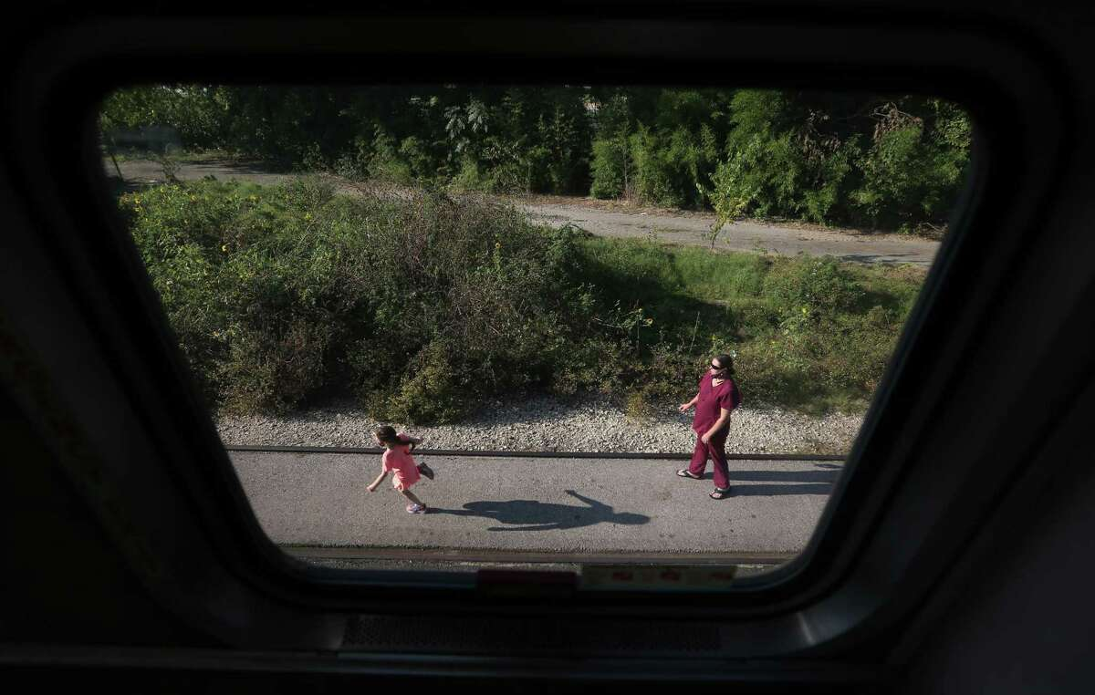 A child is seen through a window on the Texas Eagle running on the platform at the Austin Amtrak station. Amtrak officials are reducing long-distance service because ridership has plunged amid the COVID-19 pandemic.